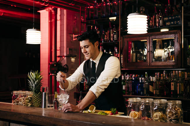 Young elegant barman working behind a bar counter mixing drinks with fruits — Stock Photo
