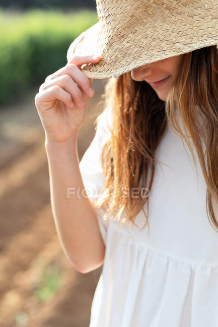Anonymous teen girl in hat on agricultural field in orchard in Catalonia, Spain — стокове фото