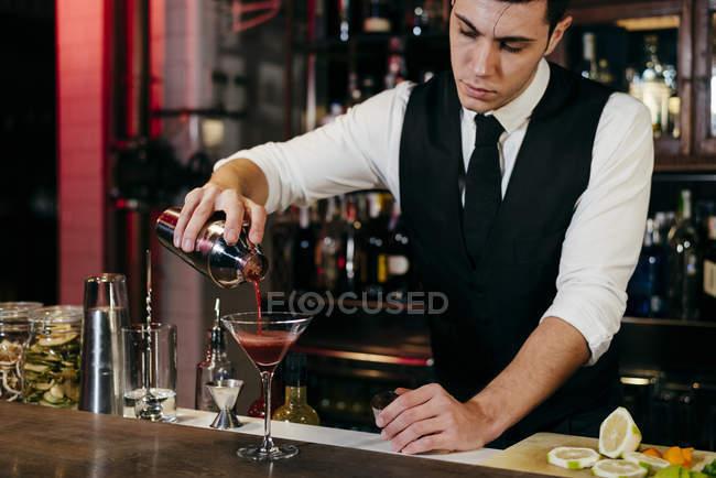 Молодий елегантний бармен, що працює за барною стійкою, наливає напій від шейкера до скла. — стокове фото