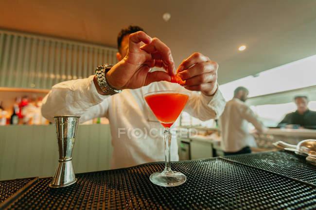 Barman che prepara cocktail all'arancia in un bar — Foto stock
