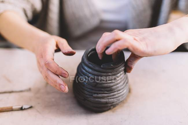 Female potter shaping vase from soft clay rolls on table — Stock Photo
