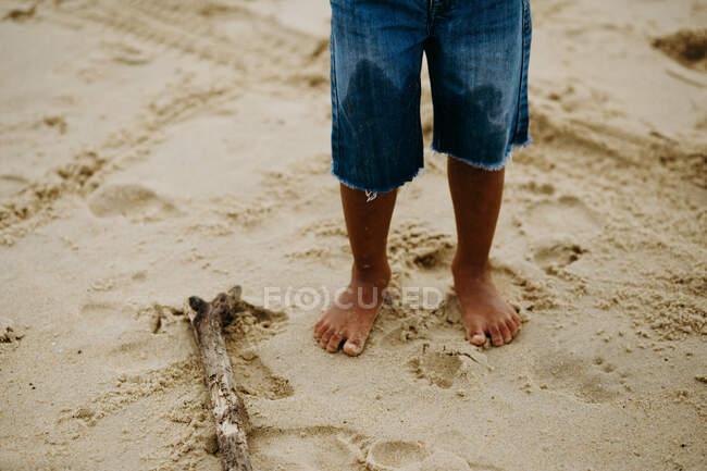 Jambes d'un garçon anonyme pieds nus en short debout sur du sable mouillé près d'un bâton de bois tout en passant du temps sur la plage — Photo de stock