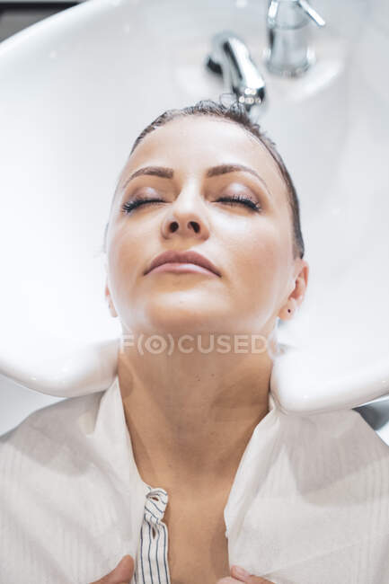 Donna sdraiata con testa in lavandino a salone di capelli — Foto stock