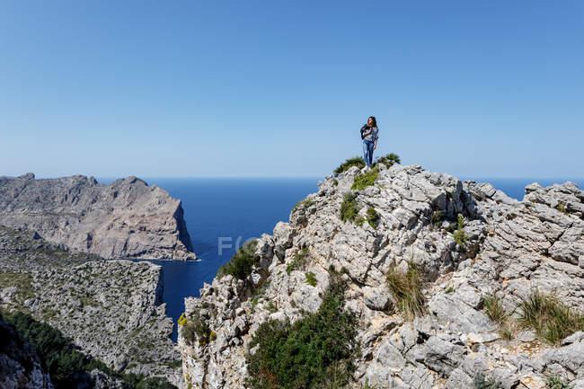 Giovane donna in piedi sulla scogliera — Foto stock