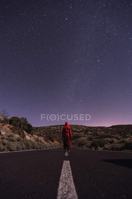 Traveler in red hooded jacket standing on empty road at night — Stock Photo