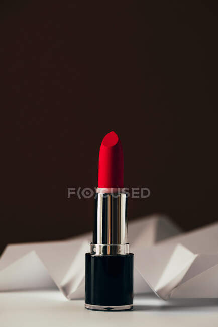 Red lipstick on raised white chevron, Product and make up contemporary concept — Stock Photo
