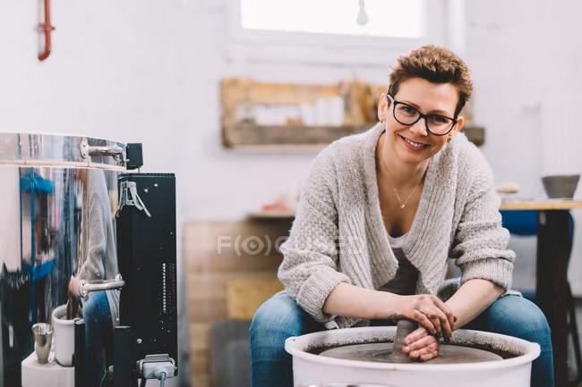 Женщина гончар с грязными руками делает глиняный горшок на колесах в мастерской — стоковое фото