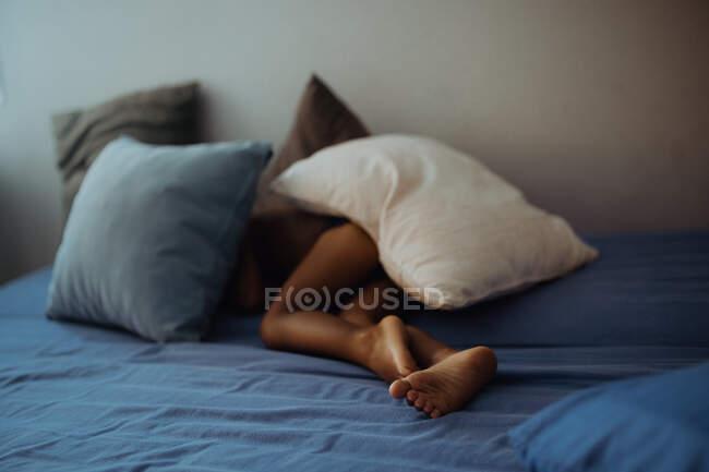 Irriconoscibile bambino scalzo sdraiato sotto cuscini su un comodo letto in camera accogliente — Foto stock