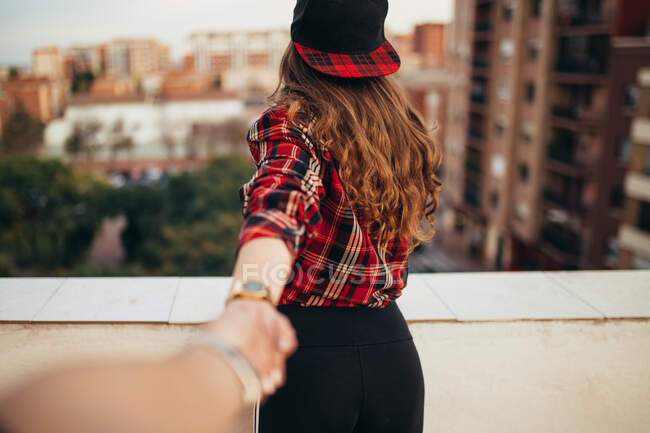 Back view of young woman in trendy outfit holding hand of anonymous friend on balcony against blurred background of modern city — Stock Photo