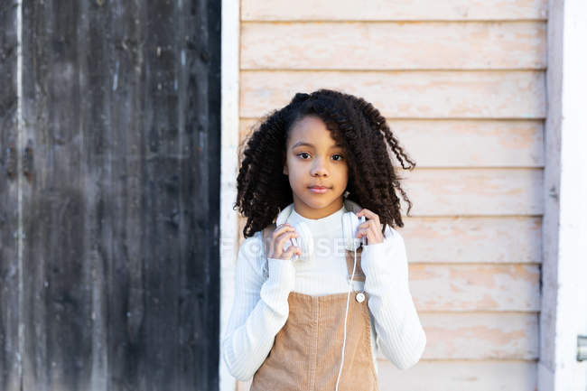 Portrait of African American girl standing with headphones against wooden wall — Stock Photo