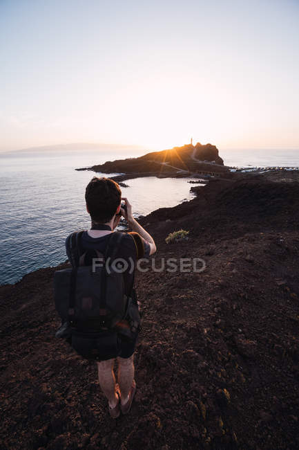 Back view of traveler with camera and backpack taking photo of rocky cliffs on seashore in sunset backlit — Stock Photo