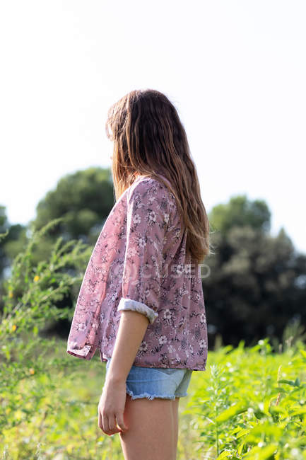 Side view of anonymous female teenager in casual outfit looking away while standing in field — Stock Photo