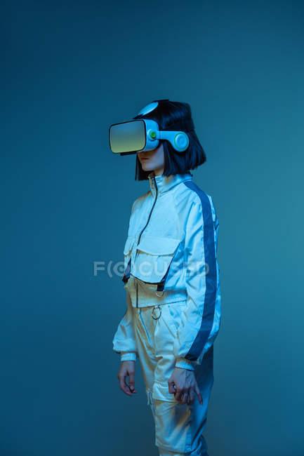 Jovem excitada com experiência de realidade virtual em luz de néon — Fotografia de Stock