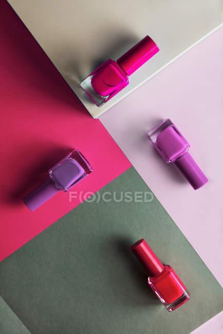 Polices à ongles multicolores sur fond de motif géométrique — Photo de stock