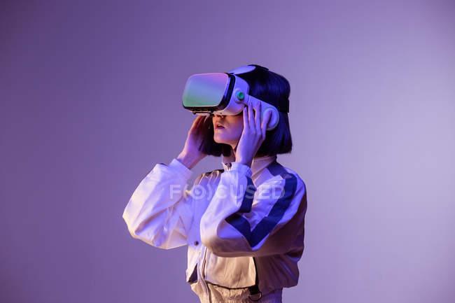 Aufgeregte junge Frau mit Virtual-Reality-Erfahrung im Neonlicht — Stockfoto