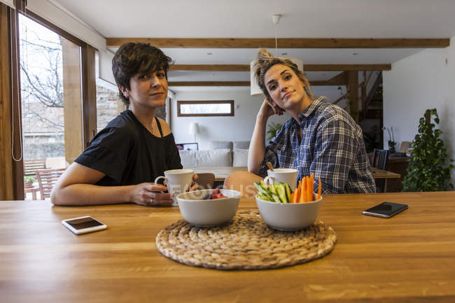 Two beautiful and young women having breakfast at home and having fun — Stock Photo