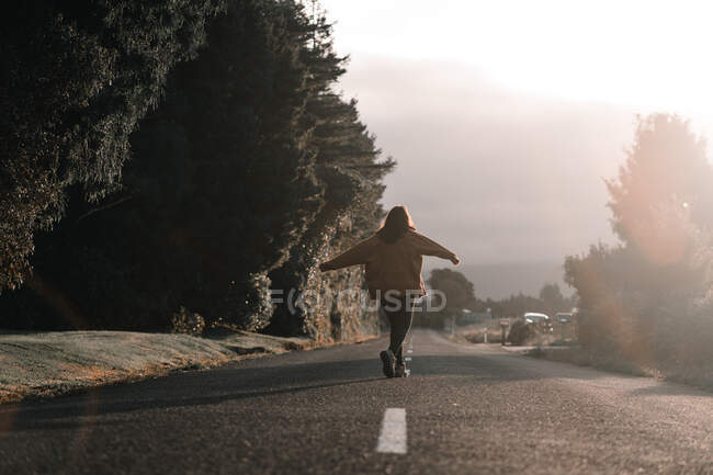 Back view of female traveler with outstretched arms walking in middle of asphalt countryside road on sunny day in Taranaki, New Zealand — стоковое фото