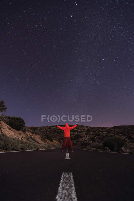 Traveler in red hooded jacket standing on empty road at night with outstretched arms — Stock Photo