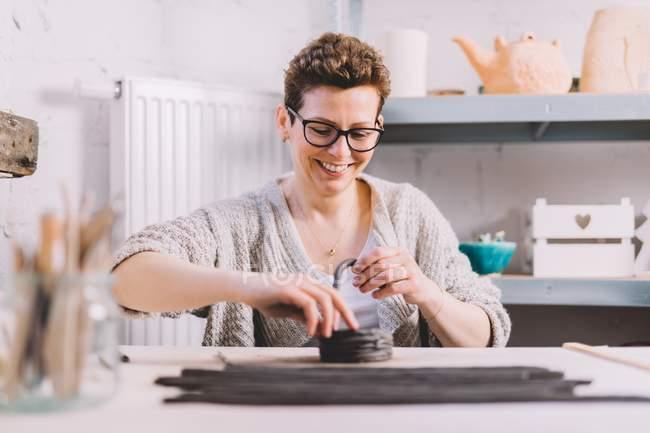 Adulto oleiro feminino colocando tira de argila macia em cima do vaso enquanto sentado à mesa na oficina — Fotografia de Stock