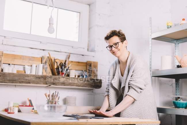 Mujer adulta en gafas sonriendo alegremente y mirando a la cámara mientras trabaja con arcilla en la mesa en el taller de alfarero - foto de stock