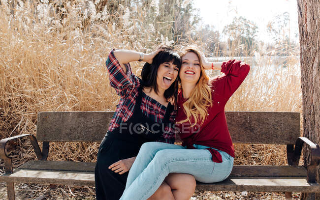 Young women sitting on bench and looking at camera — Stock Photo