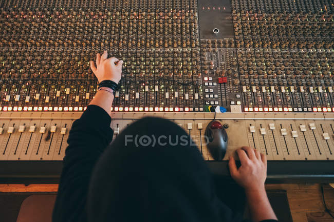 Back view of man working while playing in a equalizer instrument in a studio — Stock Photo