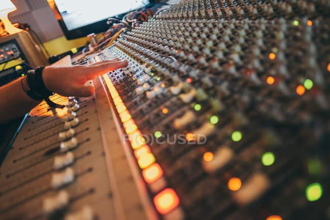 Рука неузнаваемого человека, работающего во время игры на эквалайзере в студии — стоковое фото