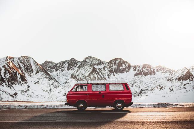 Camping-car rouge sur route de campagne asphaltée près de crête de montagne enneigée par une journée ensoleillée pendant le voyage dans la nature — Photo de stock