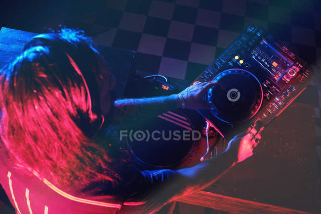 Anonymous dj man playing in a club with lights — Stock Photo