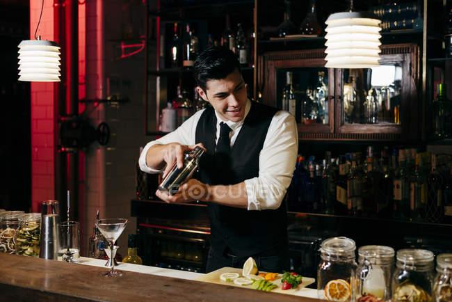 Giovane elegante barman che lavora dietro un bancone del bar mescolando bevande in uno shaker — Foto stock