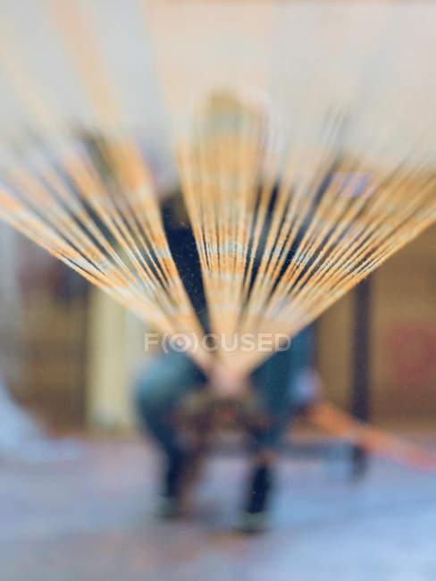 Бавовняні нитки від ткацького верстата ведуть до розмитого людини, що працюють на тканинній фабриці — стокове фото