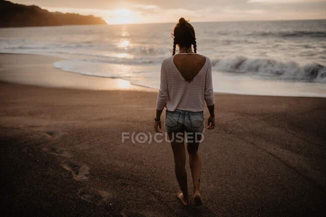 Вид на молодую женщину в повседневной одежде, идущую по песчаному пляжу к бурному морю во время заката на природе — стоковое фото