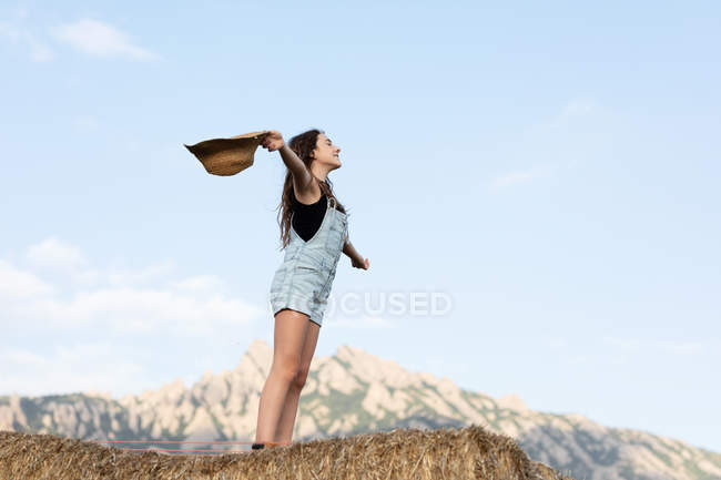 Young happy beautiful female in casual clothes throwing a hat while standing on bale of hay — стокове фото