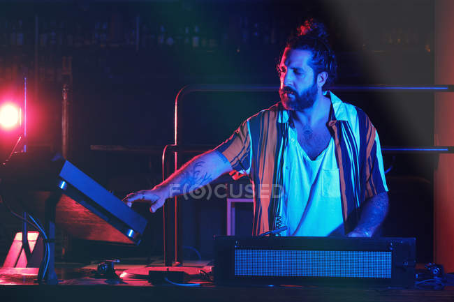 Bearded Dj man playing disco music in a club — Stock Photo