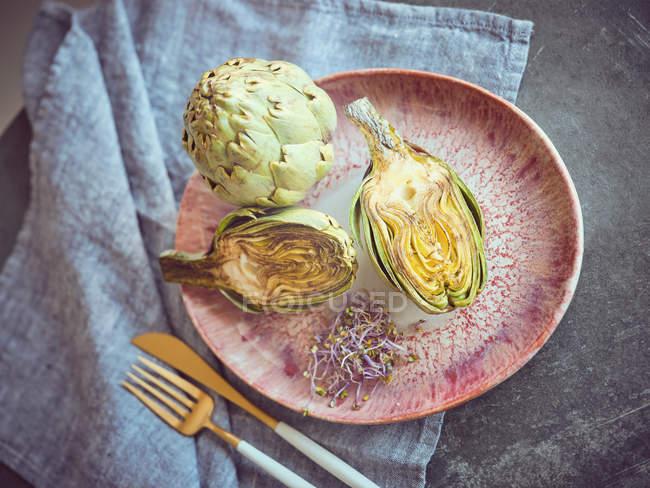 Ganze und halbierte frische Artischocken und Sprossen auf rosa Keramikplatte auf dem Tisch — Stockfoto