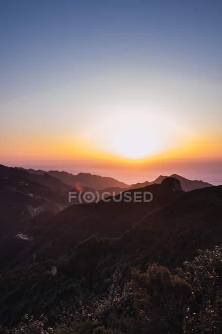 Incroyable coucher de soleil lumineux sur les montagnes côtières — Photo de stock