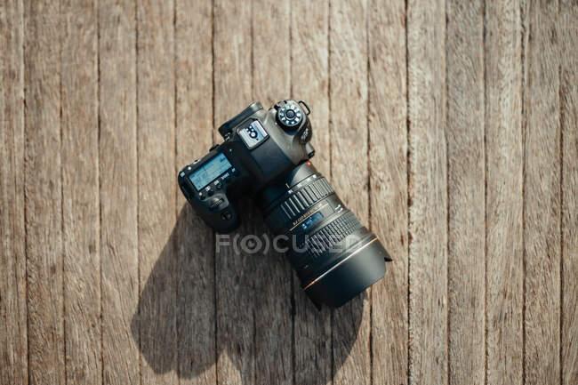 Fotocamera professionale posizionata su una superficie in legno grezzo nella giornata di sole in campagna — Foto stock