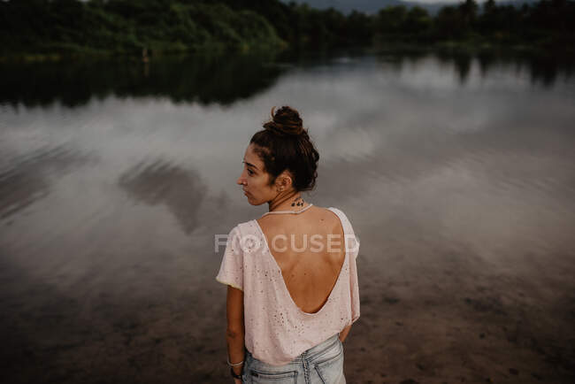 From behind view portrait of woman near pond with calm water in countryside — стокове фото