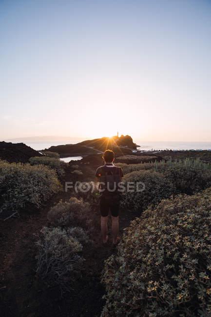 Male photographer walking on seaside at sunset — Stock Photo
