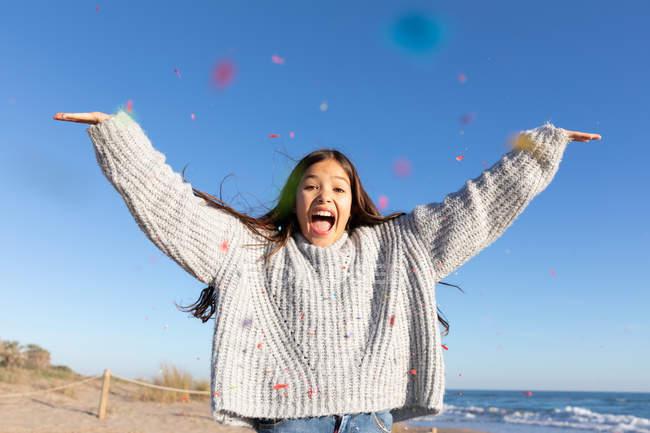 Дівчина в стильному трикотажних светр насолоджуючись падіння барвисті конфетті на вечірці сонячний день на березі моря — стокове фото