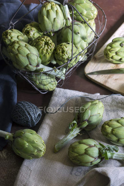 Ripe green artichokes on fabric and in metal basket on wooden table — Stock Photo