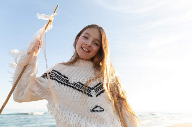 Cheerful female teenager in stylish sweater holding stick with ribbons and looking at camera on beach against cloudless blue sky — Stock Photo