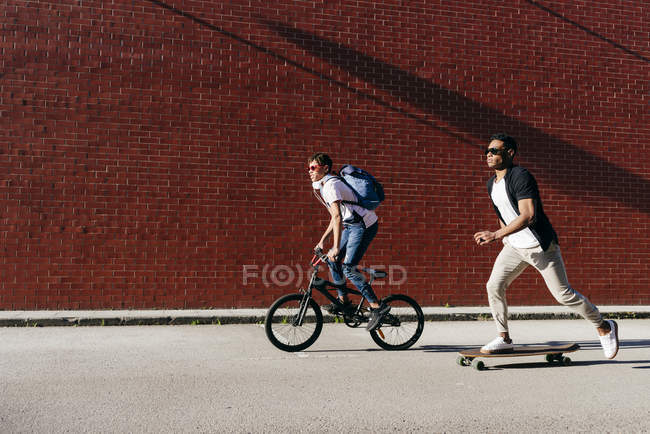 Side view of young black successful male friends in casual apparel and stylish sunglasses riding bike and skateboard — Stock Photo