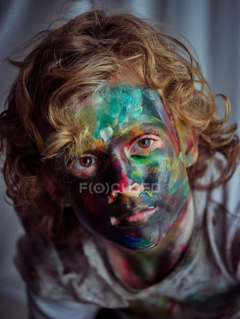 Кумедний хлопчик, пофарбований яскравими фарбами, сидить біля штор і малює на обличчі. — стокове фото