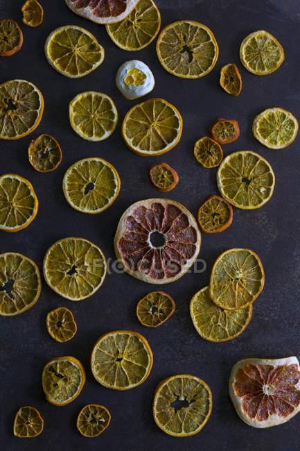 Fatias de laranjas secas e toranja colocadas na mesa cinzenta escura — Fotografia de Stock