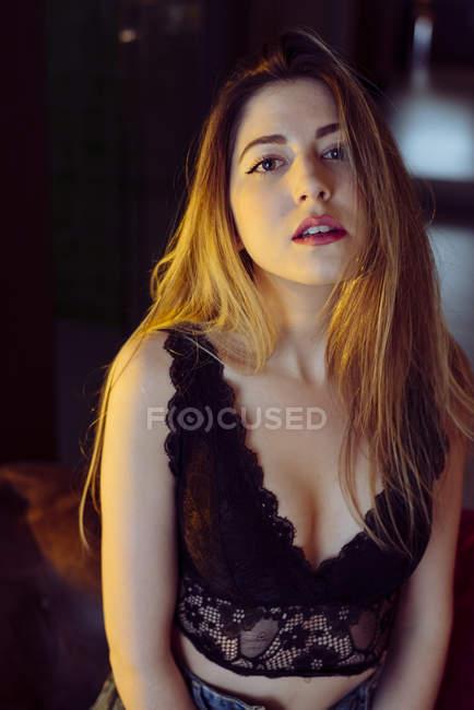 Joven seductora posando en el sofá en casa - foto de stock
