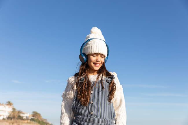 Усміхнена дівчина в навушниках і теплий капелюх прослуховування музики і перегляду смартфона, стоячи проти безхмарне небо — стокове фото