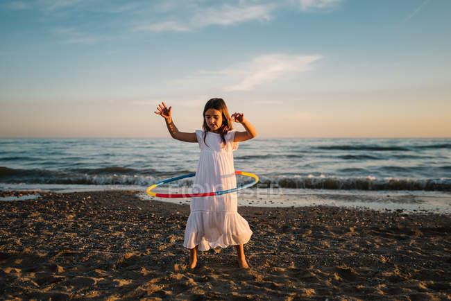 Kleines Mädchen im weißen Kleid spielt am Strand mit Hula-Hoop-Reifen vor dem Hintergrund des Abendhimmels — Stockfoto