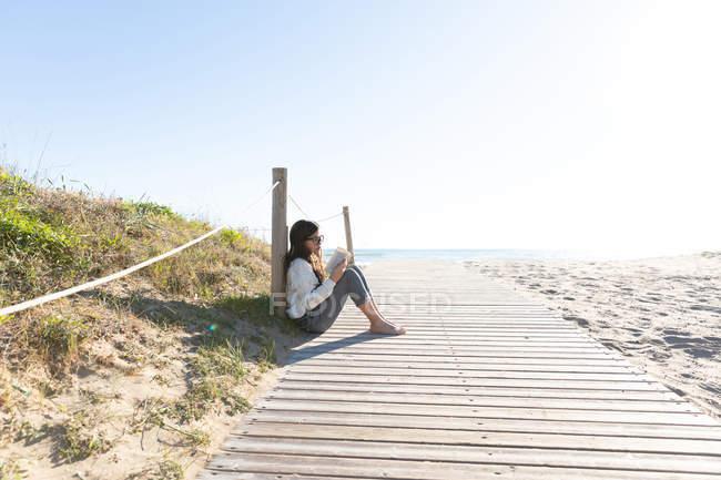 Босоніж дівчина в повсякденний одяг і окуляри читання книг, сидячи на пиломатеріалів шлях на пляжі — стокове фото