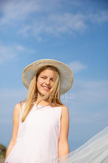 Ragazza in cappello vicino tenda da sole con cielo blu chiaro sulla sabbia sulla spiaggia — Foto stock